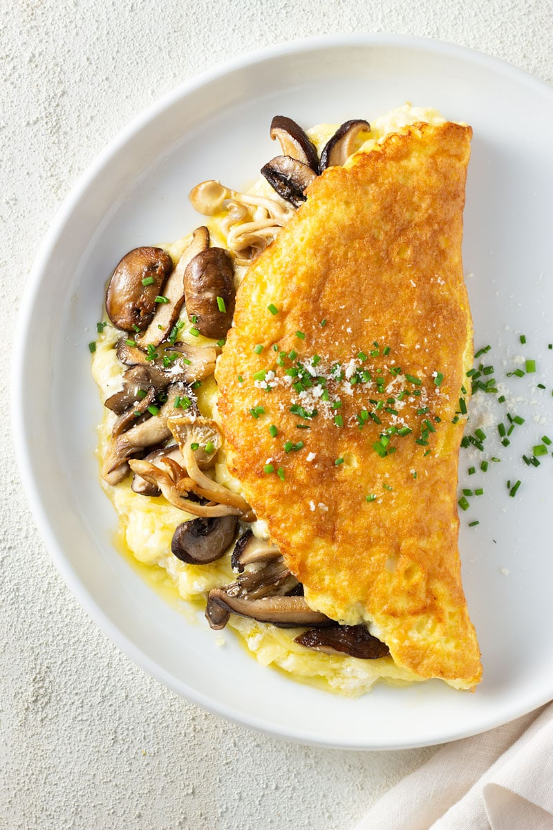 Overhead, close up view of a souffle omelet filled with parmesan cheese, gruyere cheese and mixed mushrooms and topped with chives and parmesan. It's on a white plate with an off white, textured surface, a glass of white wine and an off white towel.