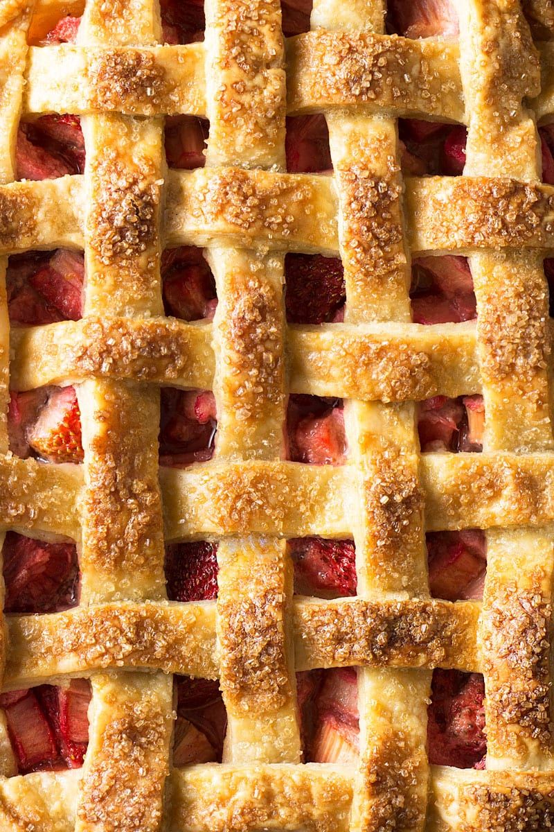 A closeup of lattice crust with strawberries and rhubarb underneath.