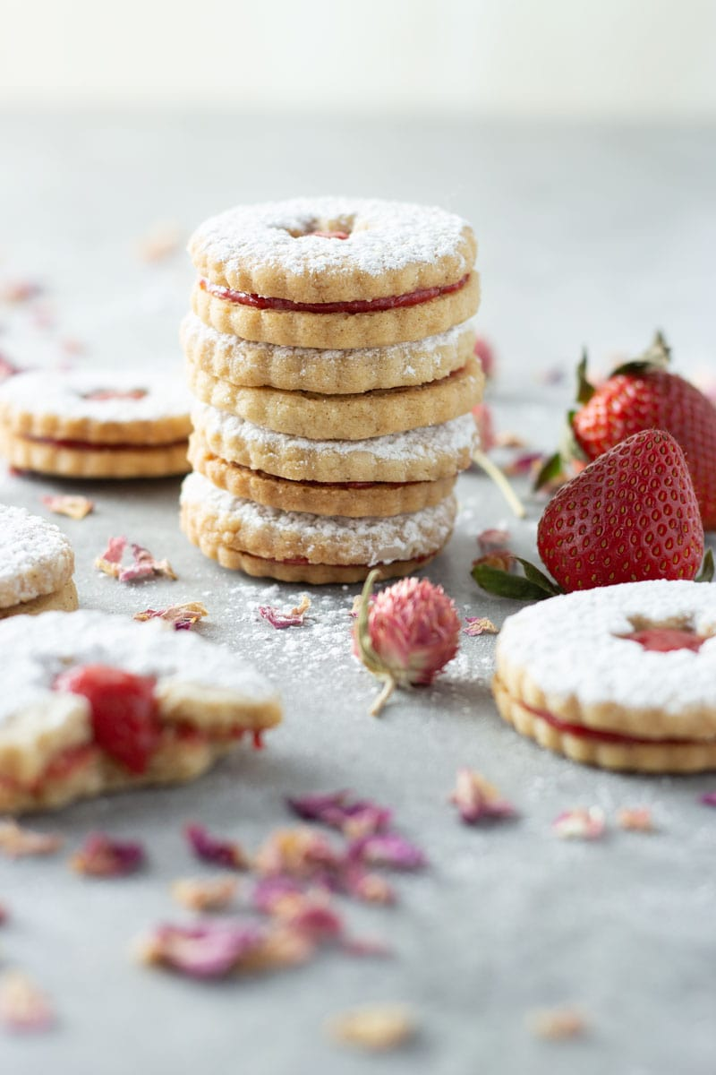 Straight on shot of a stack of linzer cookies filled with strawberry rose jam and dusted with powdered sugar surrounded by more linzer cookies, one which is partially eaten, fresh strawberries and dried flowers and rose petals. .