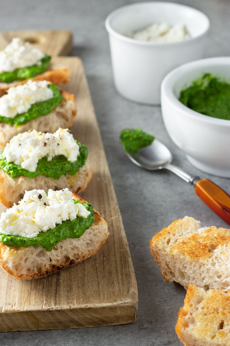 3/4 angle shot of crostini topped with ramp pesto and ricotta cheese on a light wood cutting board, surrounded by bowls of ricotta and ramp pesto, a spoon and slices of toast on a grey, textured surface.