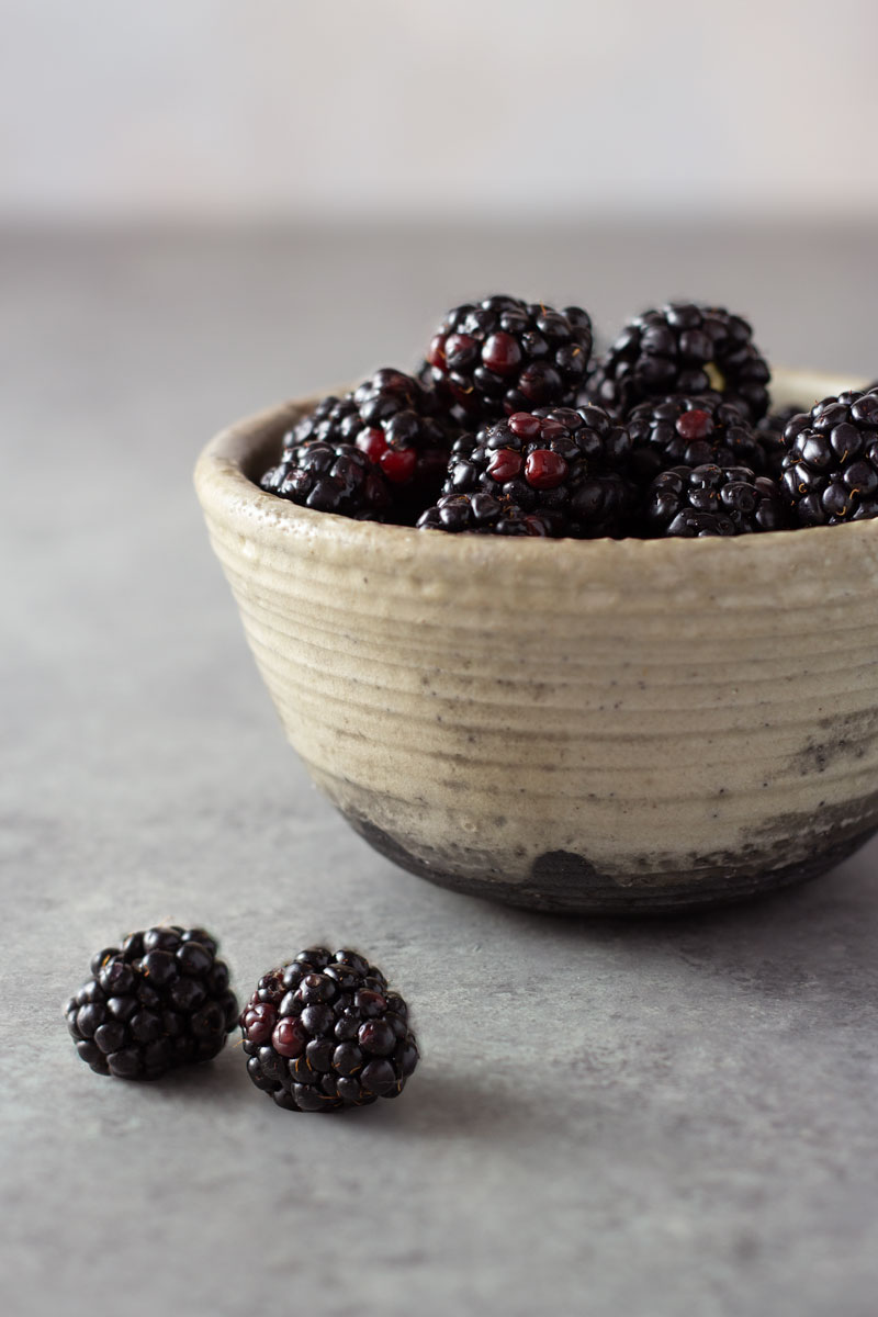 Straight on shot of a rustic bowl of fresh blackberries on a light grey surface.