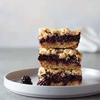 Straight on shot of a stack of blackberry crumb bars on a white plate, surrounded by fresh blackberries on a light grey surface with a textured off white background.