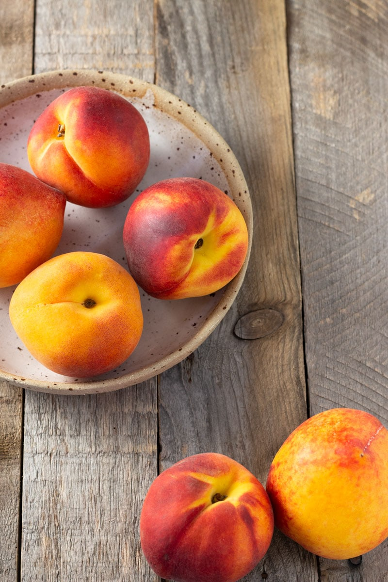 3/4 shot of a rustic bowl filled with peaches, surrounded by more peaches, on a rustic, light wood surface.