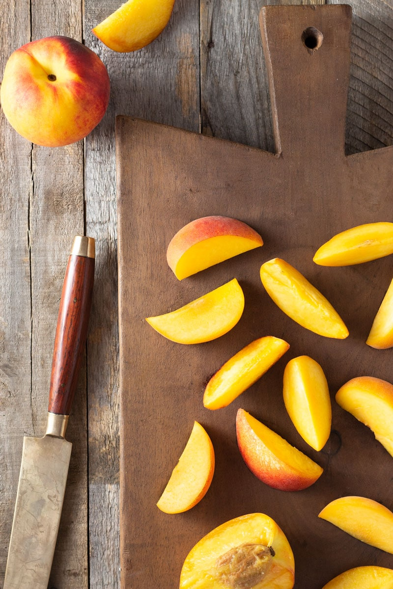 Overhead shot of sliced peaches on a vintage French, dark wood cutting board surrounded by a knife and whole peach on a rustic, light wood surface.