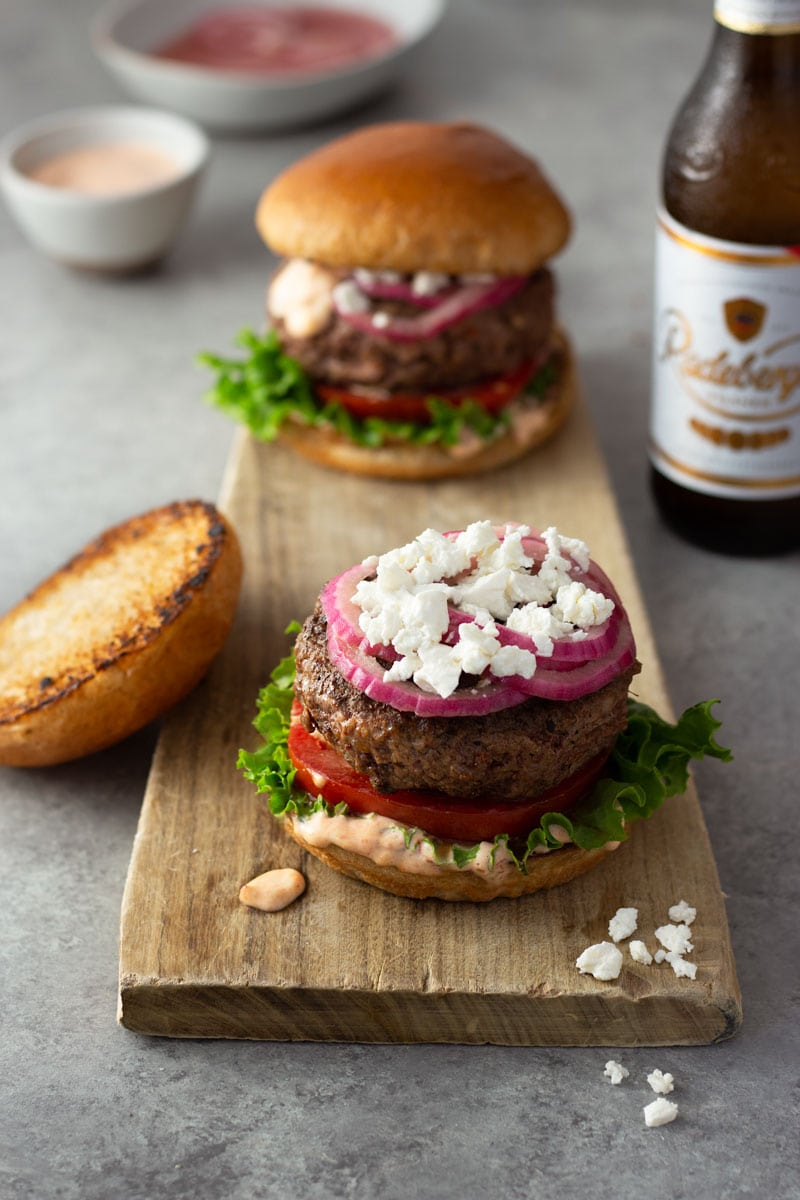 3/4 angled shot of a harissa lamb burger with spicy mayonnaise, lettuce, tomato, quick pickled red onions and feta on a brioche bun on a light wood cutting board on a light grey surface with a beer, a burger and bowls of spicy mayo and pickled onions in the background.
