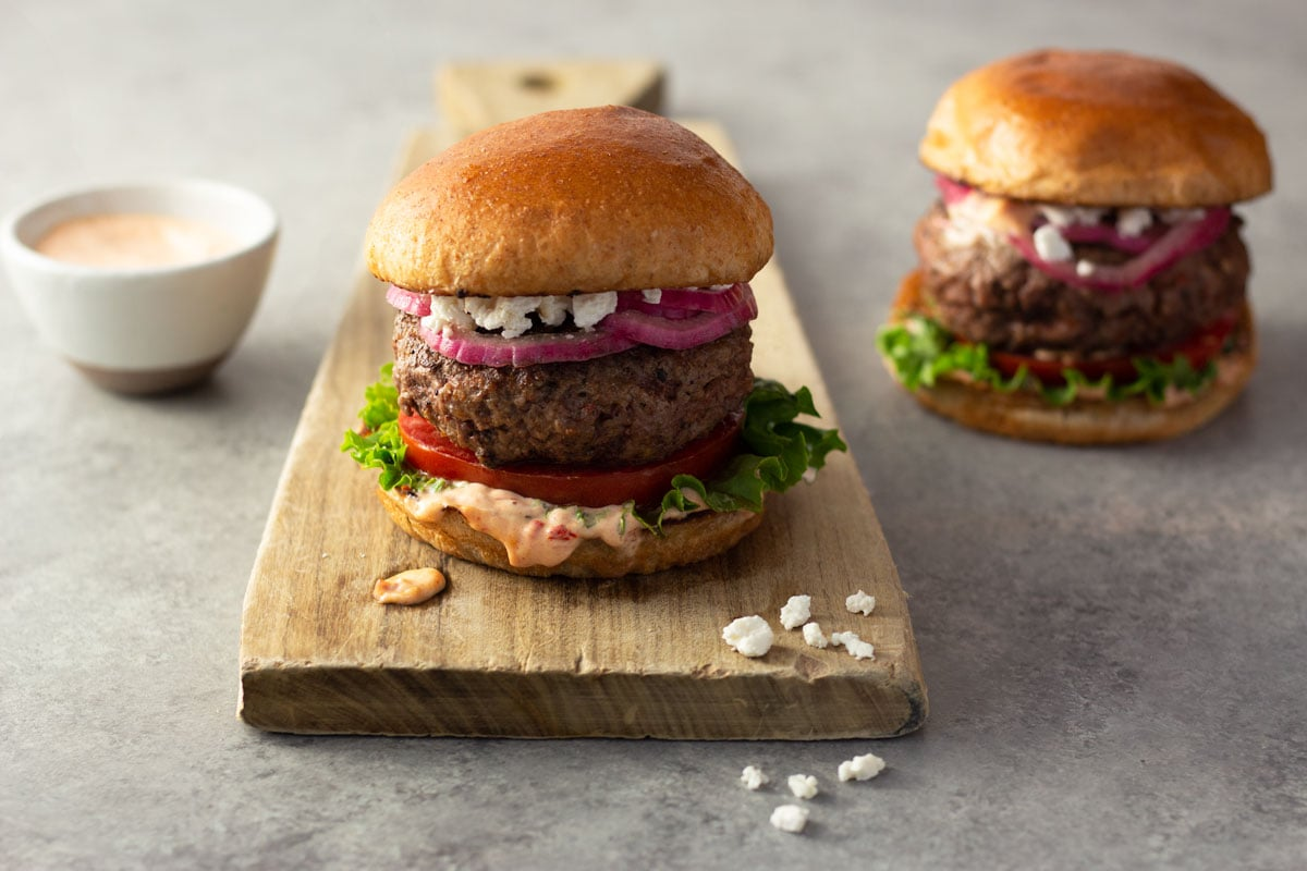 Straight on shot of a harissa lamb burger with spicy mayonnaise, lettuce, tomato, quick pickled red onions and feta on a brioche bun on a light wood cutting board on a light grey surface with a burger and a small bowl of spicy mayo in the background.