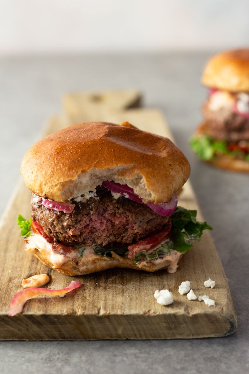 Straight on shot of a harissa lamb burger with a bite taken out of it with spicy mayonnaise, lettuce, tomato, quick pickled red onions and feta on a brioche bun on a light wood cutting board on a light grey surface with a burger in the background