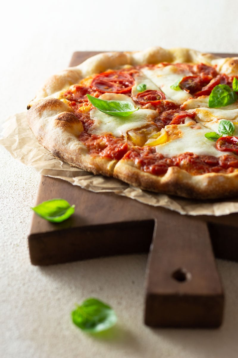 ¾ angled shot of a margherita pizza topped with colored, heirloom tomatoes, pizza sauce and buffalo mozzarella cheese on parchment on a dark wood French cutting board on an off white, textured surface.