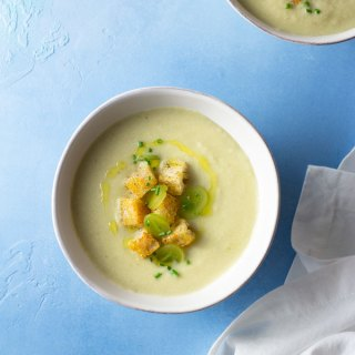 Overhead shot of two bowls of white gazpacho or ajo blanco made of cucumber, grapes, almonds and garlic, and garnished with croutons, sliced green grapes, chives and olive oil in white bowls on a light blue, textured surface surrounded by a white dish towel.