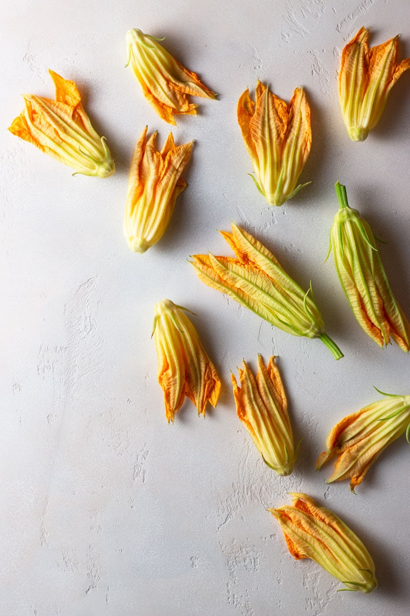Overhead shot of raw squash blossoms on a light, textured surface.