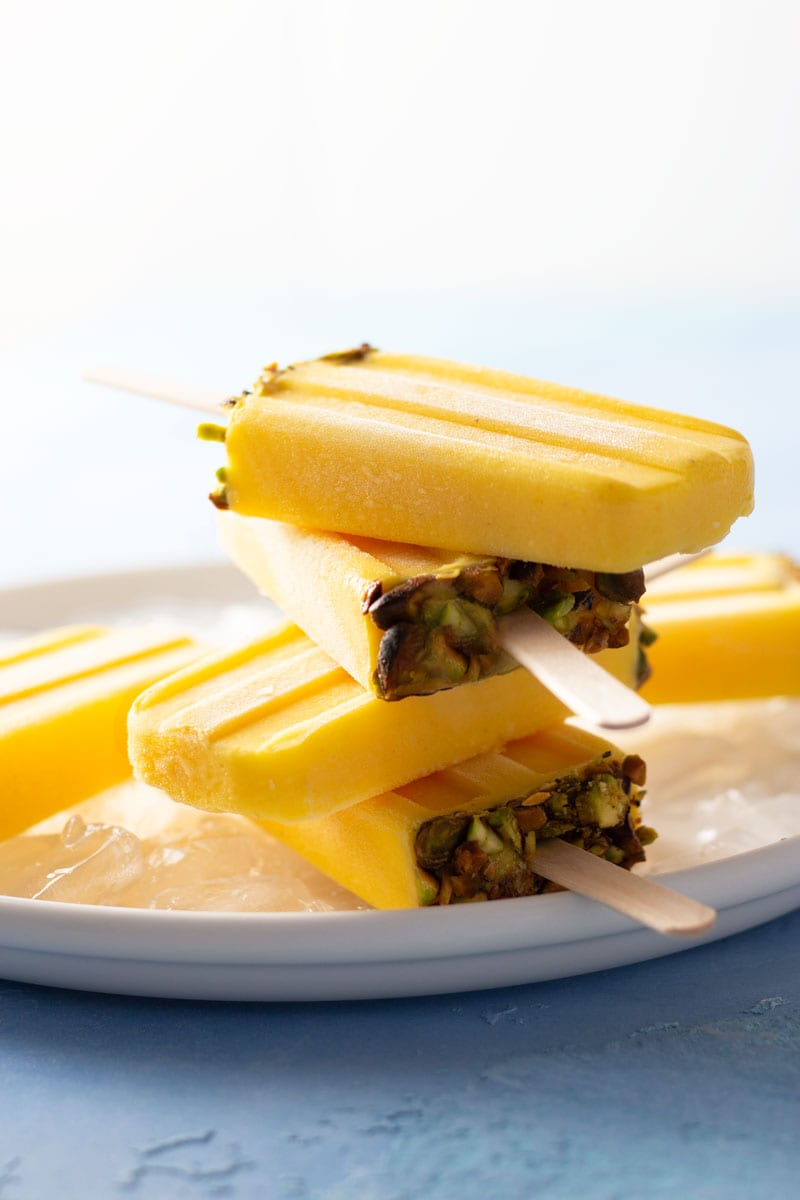 Straight on shot of Mango Lassi Popsicles with pistachios on ice on a white plate on a bright blue, textured background.
