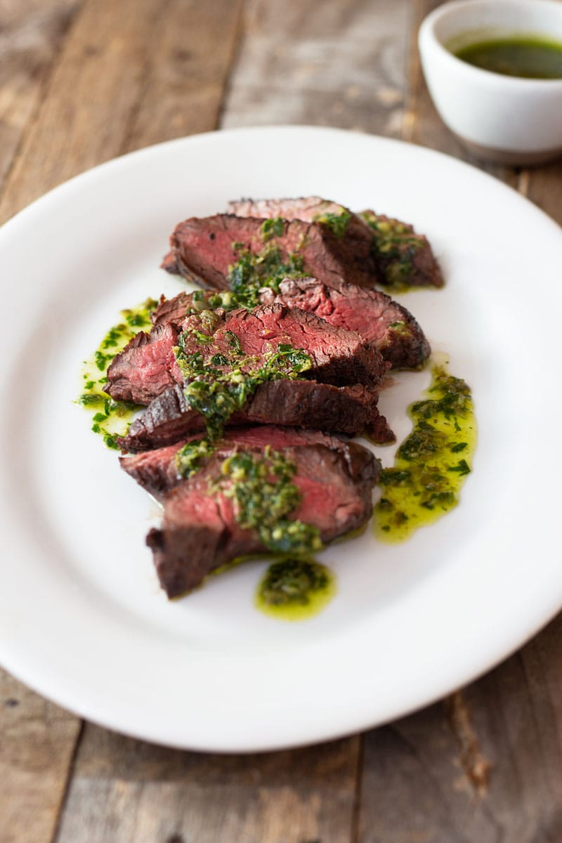 3/4 angled shot of sliced hanger steak drizzled in an Italian salsa verde on a light, rustic wood surface near a small bowl of salsa verde.