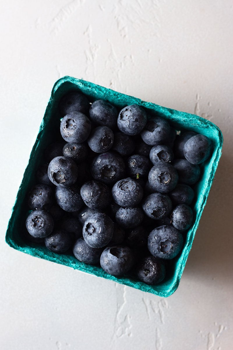 Overhead shot of a carton of blueberries with water mist on them on a light, textured surface.