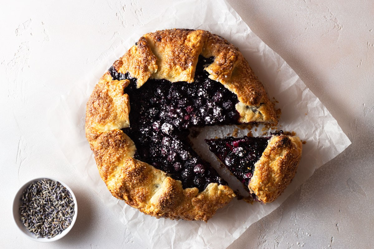 Overhead shot of a lavender blueberry galette with a slice cut out on parchment paper on a light, textured background next to a small bowl of dried lavender.