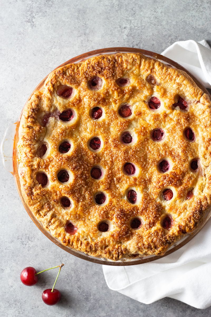 Overhead shot of a sour cherry pie with circle cut outs in the crust in a glass baking pan on a grey textured surface surrounded by a white dish towel and fresh cherries.