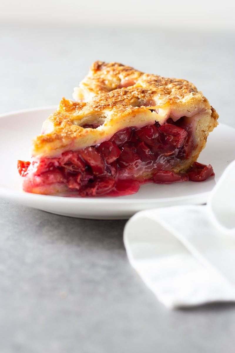 Straight on shot of a slice of sour cherry pie with circle cut outs in the crust on a white plate on a grey textured surface surrounded by a white dish towel.