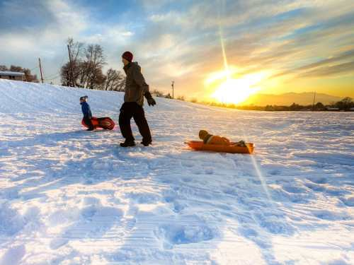 family sledding at sunset