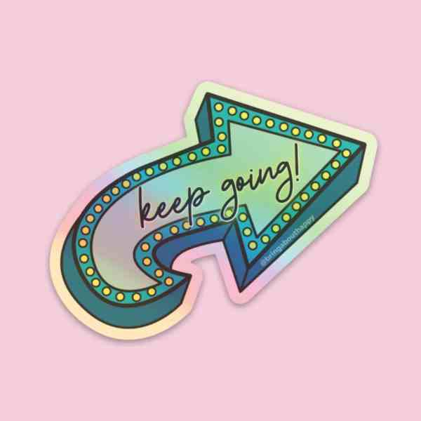 Holographic sticker that says keep going in a cute cursive font displayed on a pink background