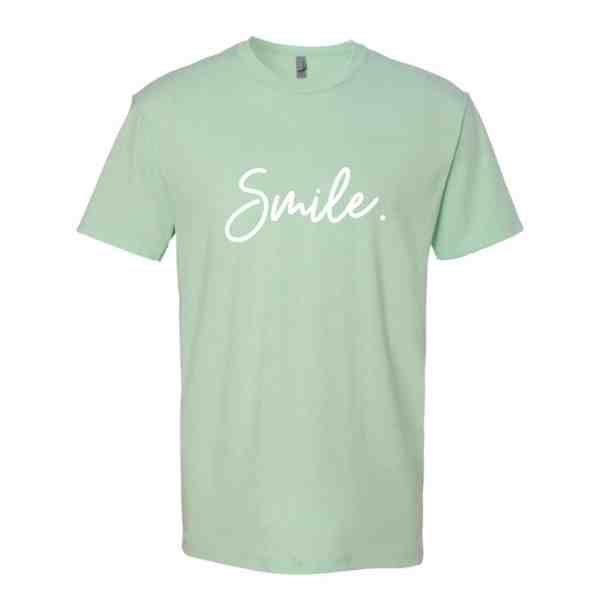 A mint green shirt with Smile written in white cursive font