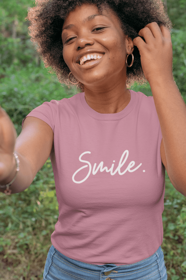 A smiling woman wearing a mauve shirt with smile written in cursive