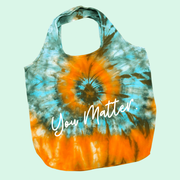 Green and yellow tie dye bag with you matter written in white cursive