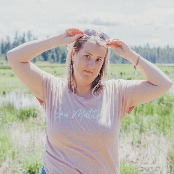 Woman standing in a field wearing a You Matter Scoop Neck TShirt Desert Rose