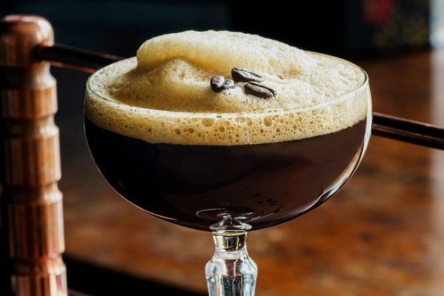 A large glass of espresso martini with coffee beans on top