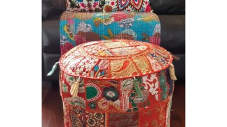 red patchwork pouf in front of couch with colourful throw and cushions