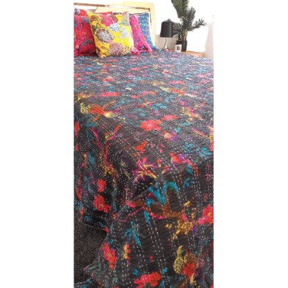 Black and patterned bed spread with coloured cushions