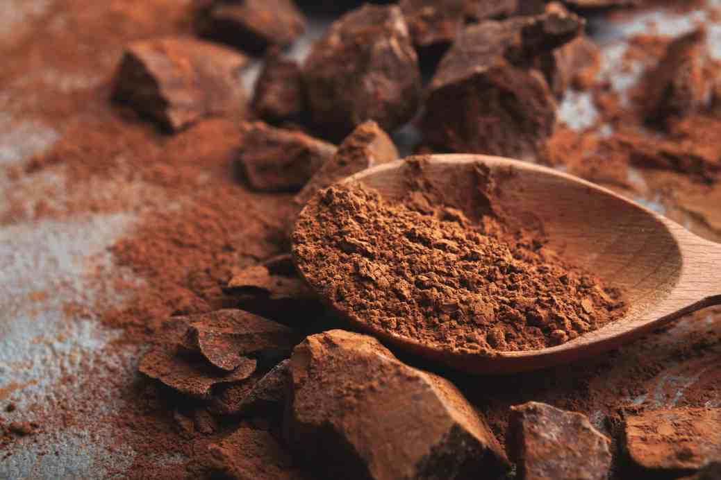 Dark chocolate pieces crushed on dark background and cocoa powder closeup
