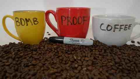 yellow cup, red cup, white cup spells out bomb proof coffee white background coffee beans foreground