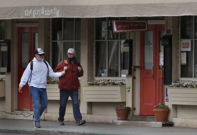 Neighbors Robert Tosti, left, and Ed Colteaux walk by The Girl and the Fig restaurant, which was temporarily closed on Thursday, Feb. 11, 2021. (Beth Schlanker/ The Press Democrat)