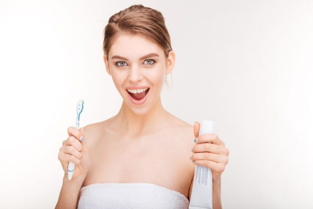 A woman holding a toothbrush and a toothpaste tube - Mississauga Dentist - Bristol Dental