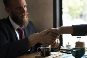Two people shaking hands in a coffee shop