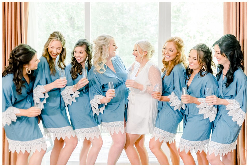 bride laughing with bridesmaids while getting ready