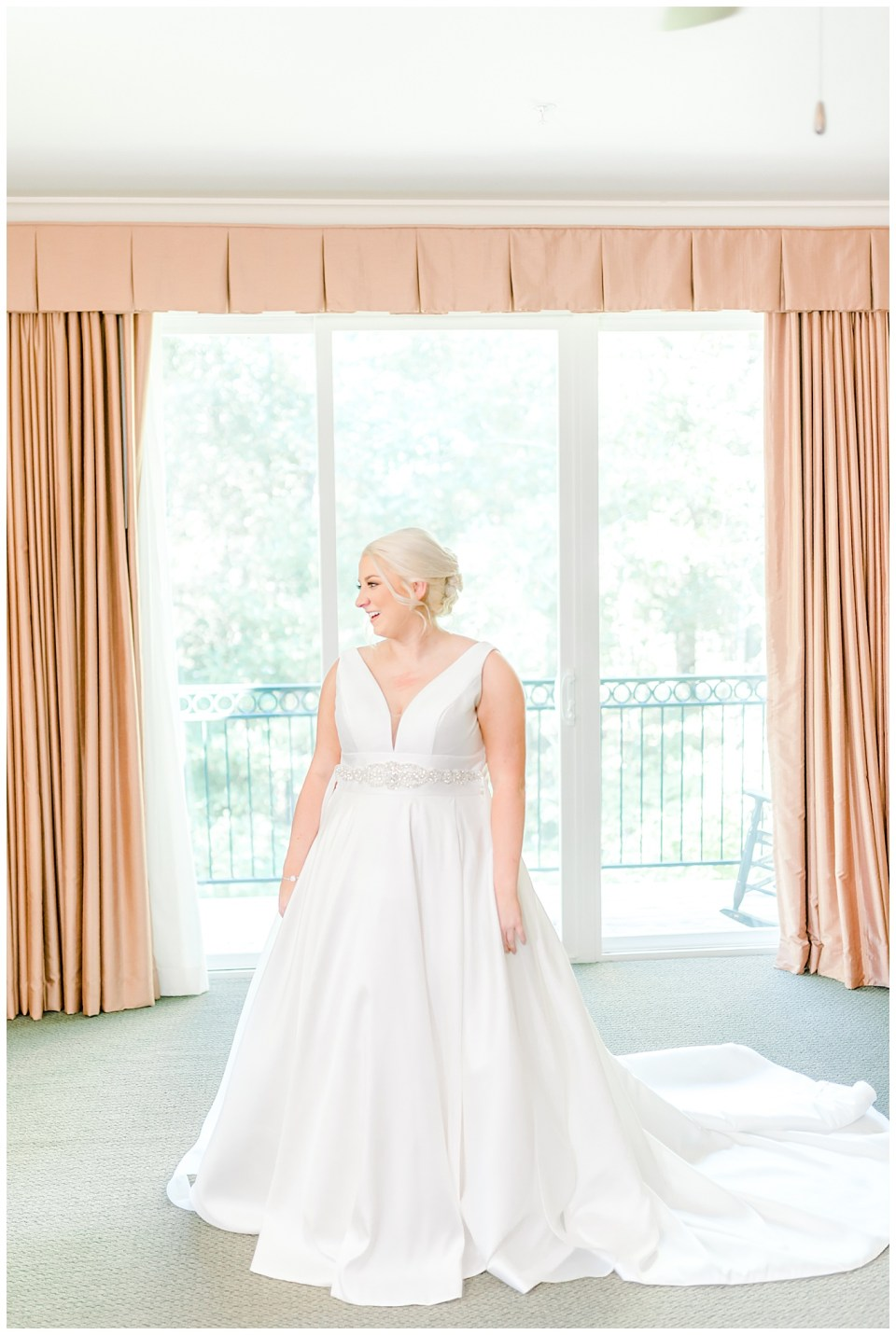 bride dressed and standing in front of window
