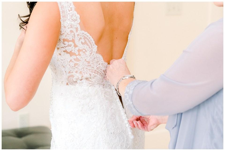 brides mom zipping up her dress