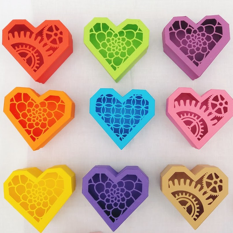 Handmade paper heart boxes in red, green, purple, orange, blue, pink, yellow, purple and beige.