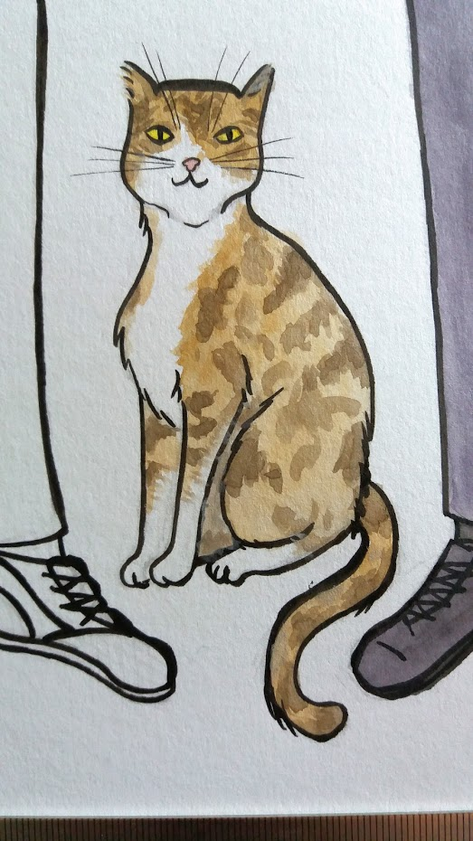 A closeup of the cat in the wedding portrait, the cat is brown, ginger and white in colour, it sits proudly between its two owners.