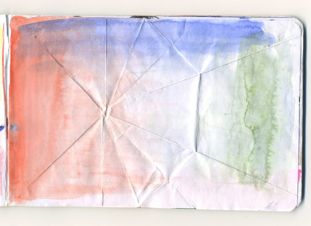 A folded page with watercolour textures caused by pooling in the folds.