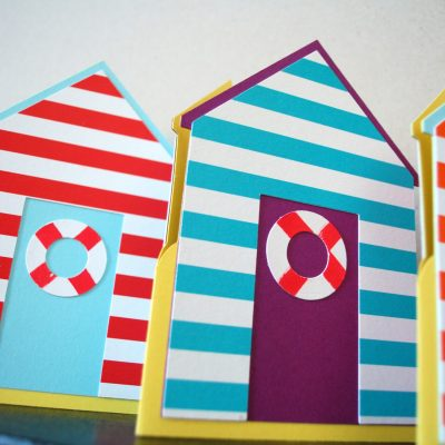 Beach Hut cards, lined up fron the front, pastel blue with red stripes, purple with blue stripes, pastel blue with orange stripes.