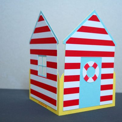Beach Hut card, pastel blue with red stripes, half side view.