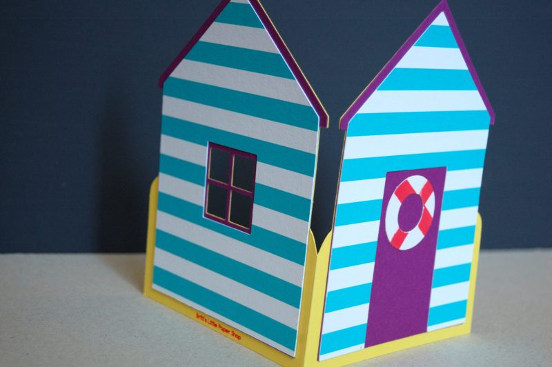 Beach Hut card, purple with blue stripes, showing the life ring detail.