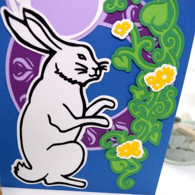 Moonlight Rabbit Greetings Card, layered paper cut design, details view, showing the green vines and yellow flowers.