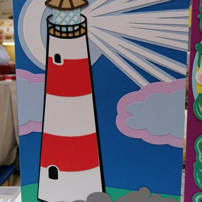 Lighthouse Greetings card pictured at market with other cards.