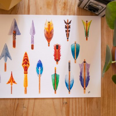 A print of the Arrows watercolour artwork next to a plant.