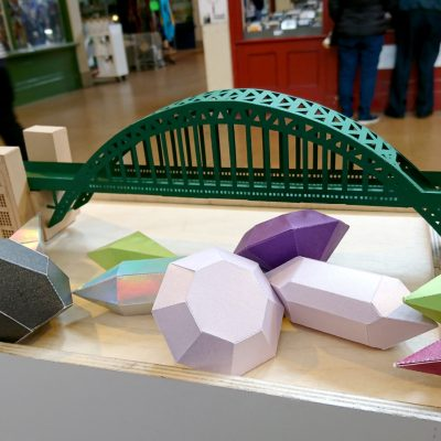 Tyne Bridge Activity Kit using green and tan card, picture from the front on display with other 3D paper shapes.