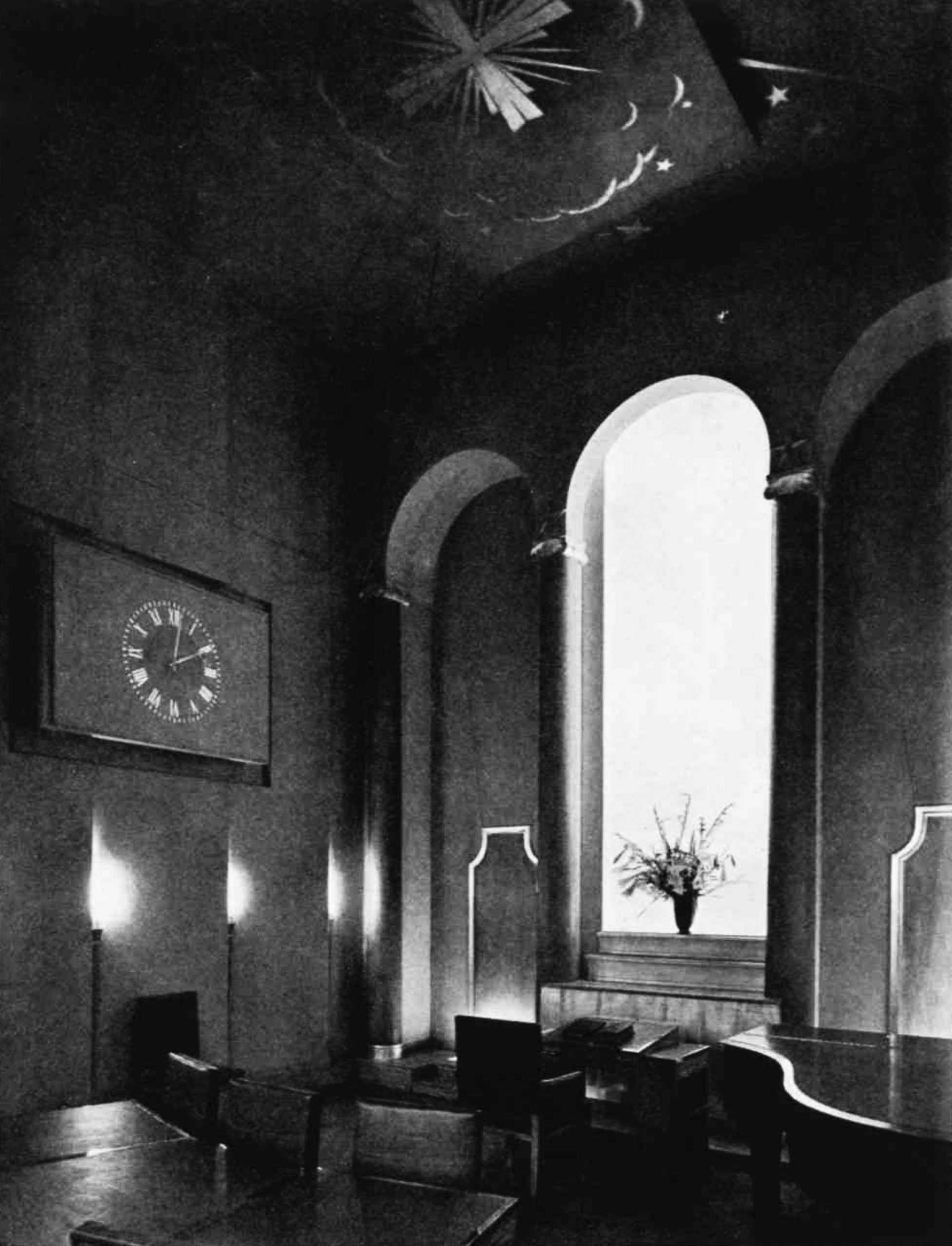 A room with alcoves - one bright - desks and chairs and a large clock