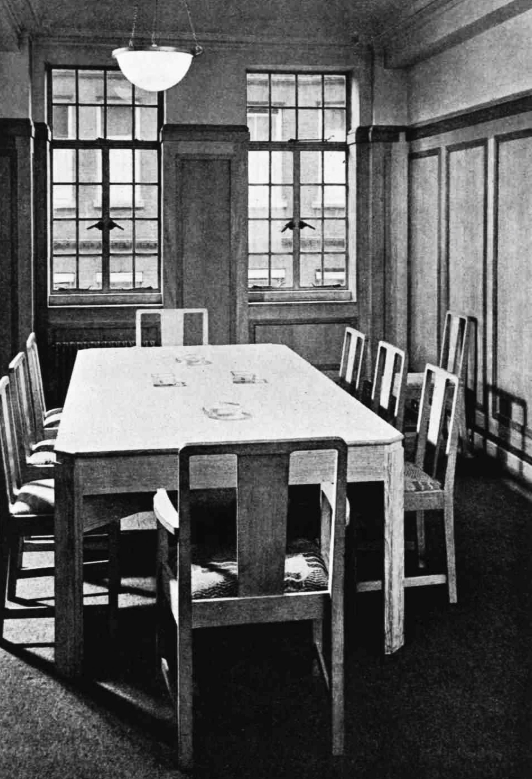 A boardroom with a table surrounded by straight-backed chairs