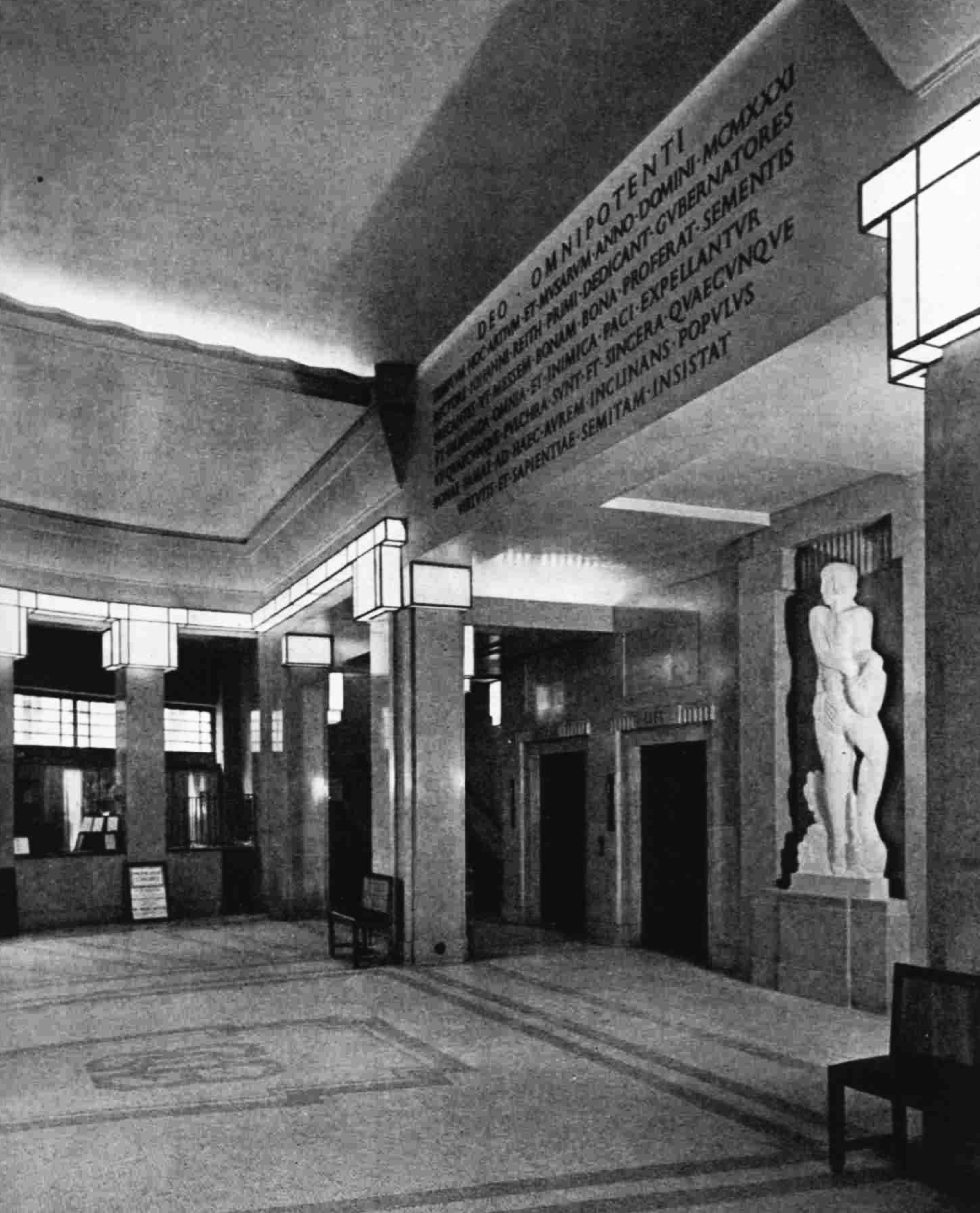 A wide space with carved text on the ceiling support and a recessed statue